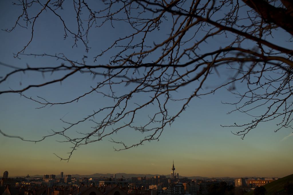 A layer of smog covers the skyline, as the sun sets in Madrid, Wednesday, Dec. 28, 2016. Madrid's town hall hopes to sharply reduce pol...