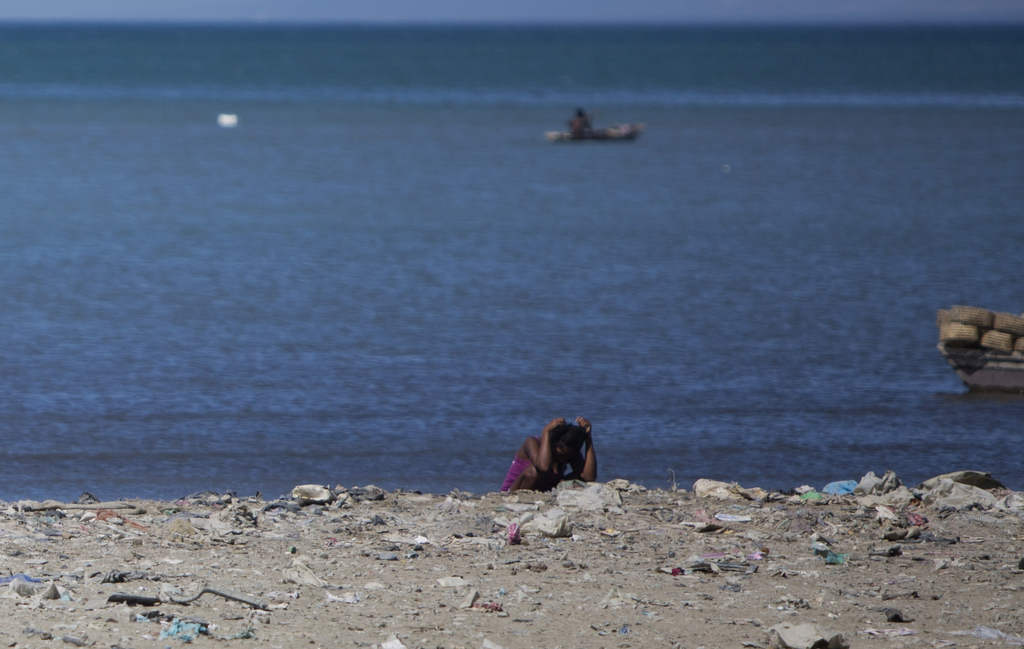 In this Dec. 25, 2016 photo, a woman defecates along the shoreline in Cite Soleil slum, in Port-au-Prince, Haiti. In a country where fl...