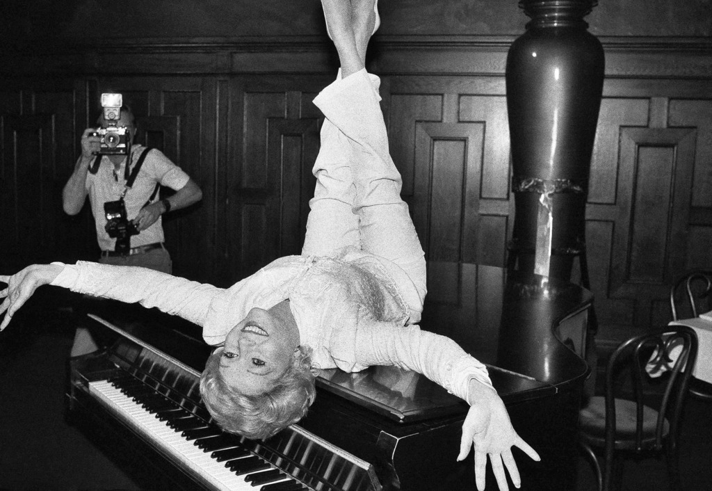 FILE- In this Sept. 8, 1982, file photo, actress Debbie Reynolds poses on a grand piano at a New York restaurant, as she promotes the r...