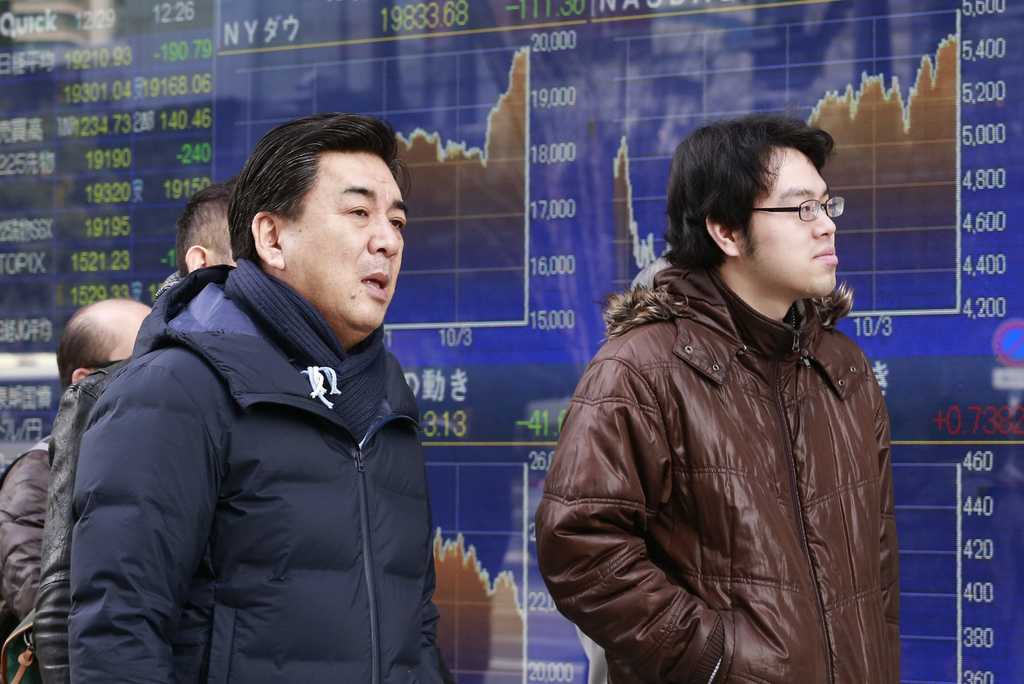 People walk past an electronic stock indicator of a securities firm in Tokyo, Thursday, Dec. 29, 2016. Asian shares drooped in thin tra...