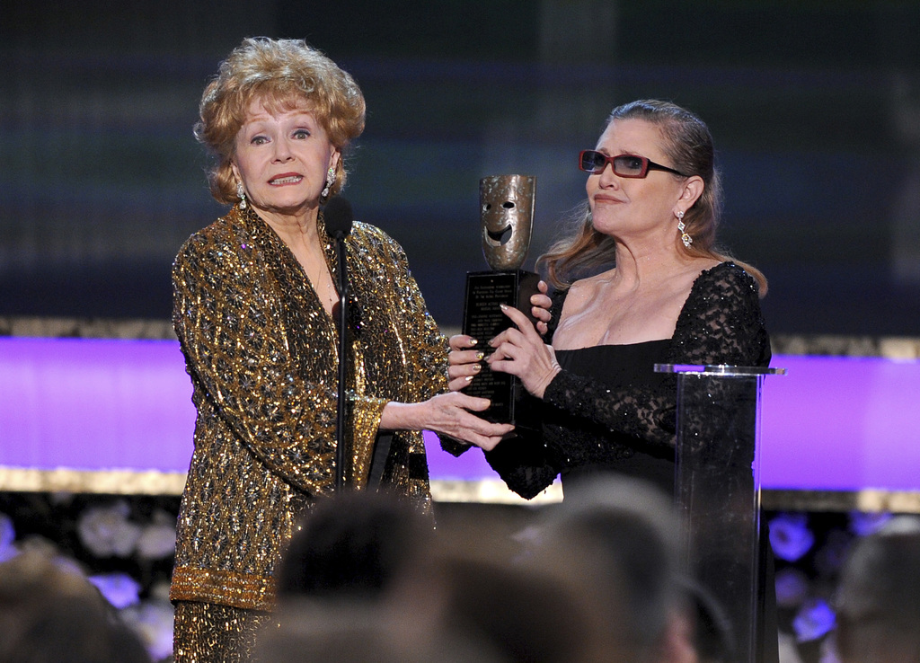 FILE- In this Jan. 25, 2015, file photo, Carrie Fisher, right, presents her mother Debbie Reynolds with the Screen Actors Guild life ac...