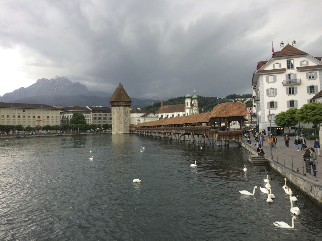 This June 15, 2016, photo provided by Albert Stumm shows swans and the Chapel Bridge in Lucerne, Switzerland. The compact city has pres...