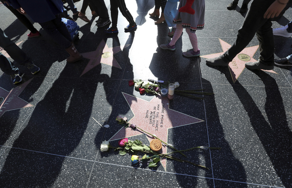 People walk past an impromptu memorial created on a blank Hollywood Walk of Fame star by fans of late actress and author Carrie Fisher,...