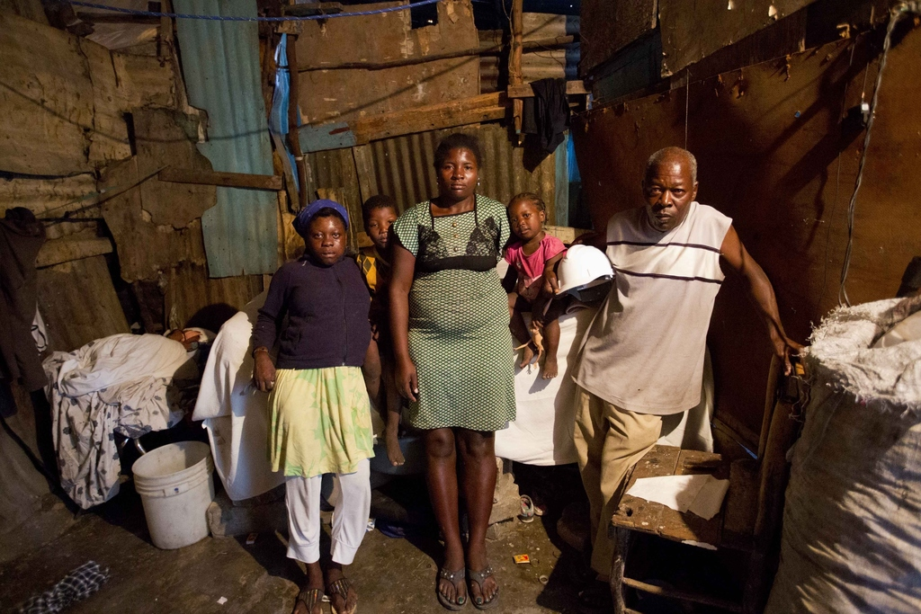 "In this Dec. 22, 2016 photo, ""bayakou"", or waste cleaner, Auguste Augustin, right, his wife Chellade Marceda, center, their children, S..."