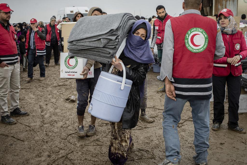 Iraqis displaced from Mosul receive aid distributions at near Qayara, Iraq on Wednesday, Dec. 28, 2016. (AP Photo/Cengiz Yar)          ...