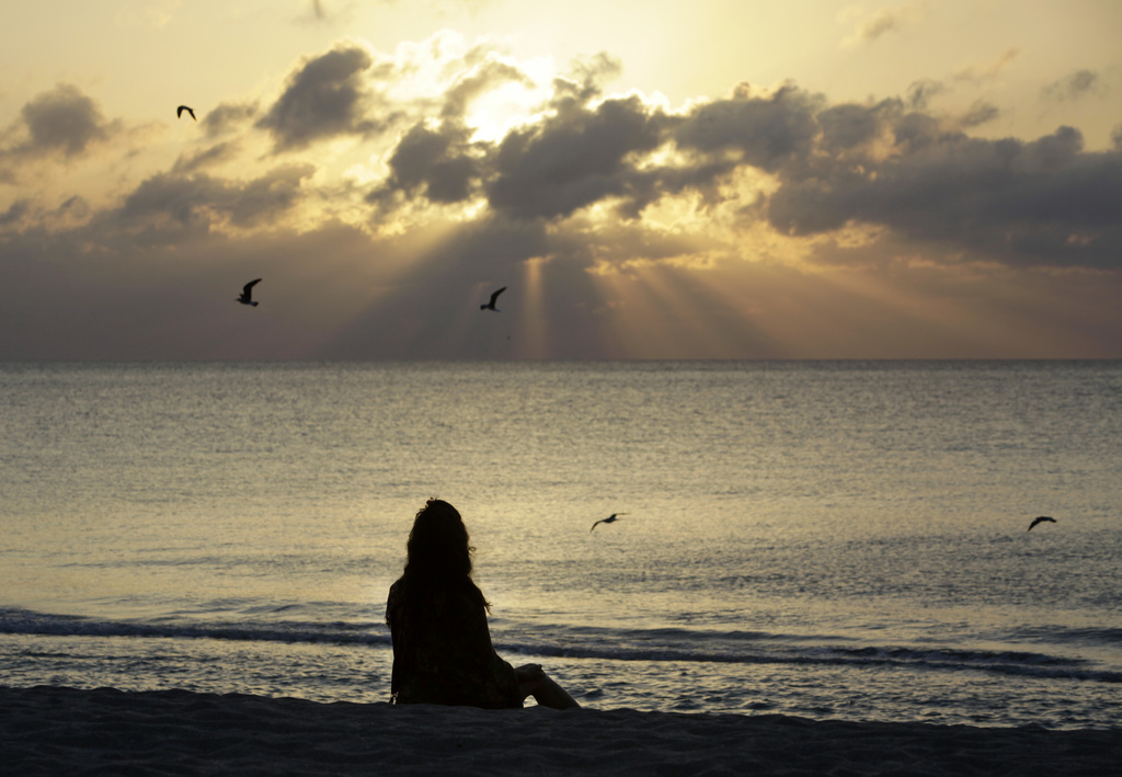 FILE - In this Wednesday, April 28, 2010, file photo, a woman meditates on the beach in Miami Beach, Fla. Mindfulness and meditation ca...