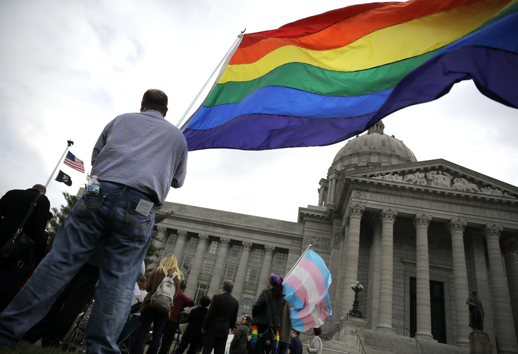 """FILE - In this March 31, 2016, file photo, gay-rights supporter Mathew """"Skippy"""" Mauldin holds a flag during a gay rights rally outside ..."""