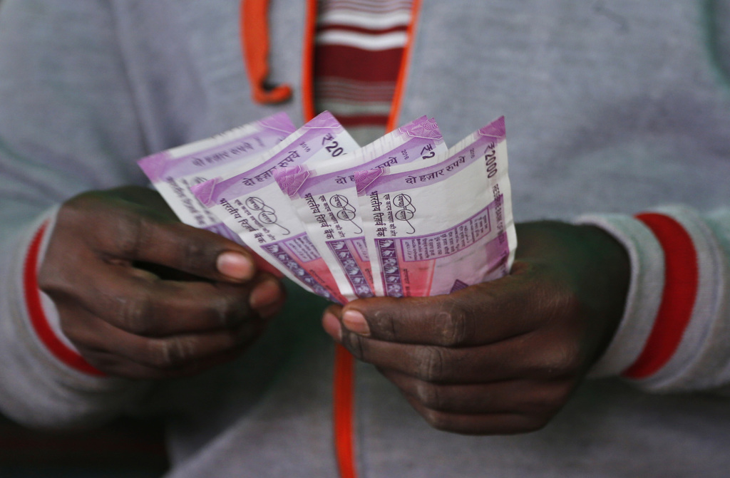 A trader counts new 2,000-rupee notes at a wholesale vegetable market in Bangalore, India, Friday, Dec. 30, 2016. India yanked most of ...