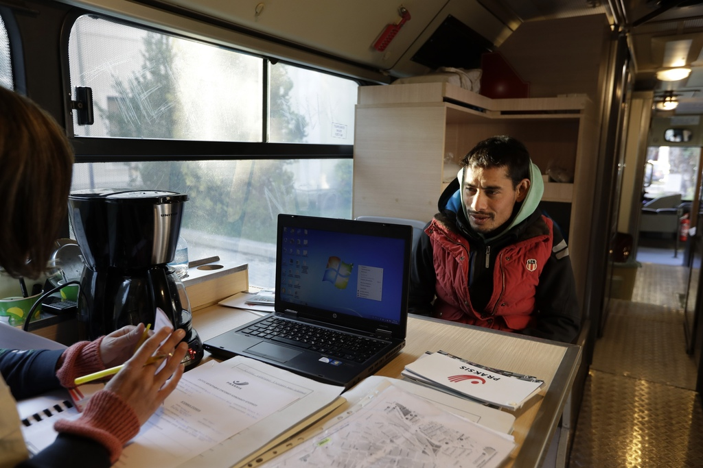 In this photo taken on Monday, Dec. 19, 2016, a homeless person talks with a social worker on the shower bus, run by the Greek Praksis,...