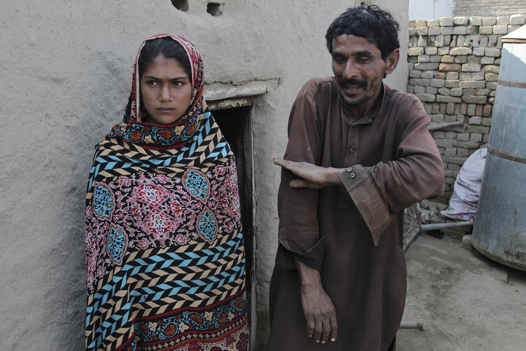 In this Tuesday, Dec. 20, 2016 photo, Mohammad Ramzan points out the height of his young bride Saima, left, when she was married to him...