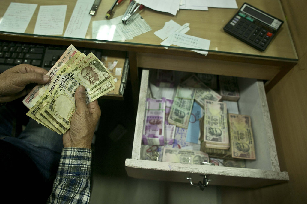 A bank official counts discontinued notes in a bank in Gauhati, India , Friday, Dec. 30, 2016. India yanked most of its currency bills ...