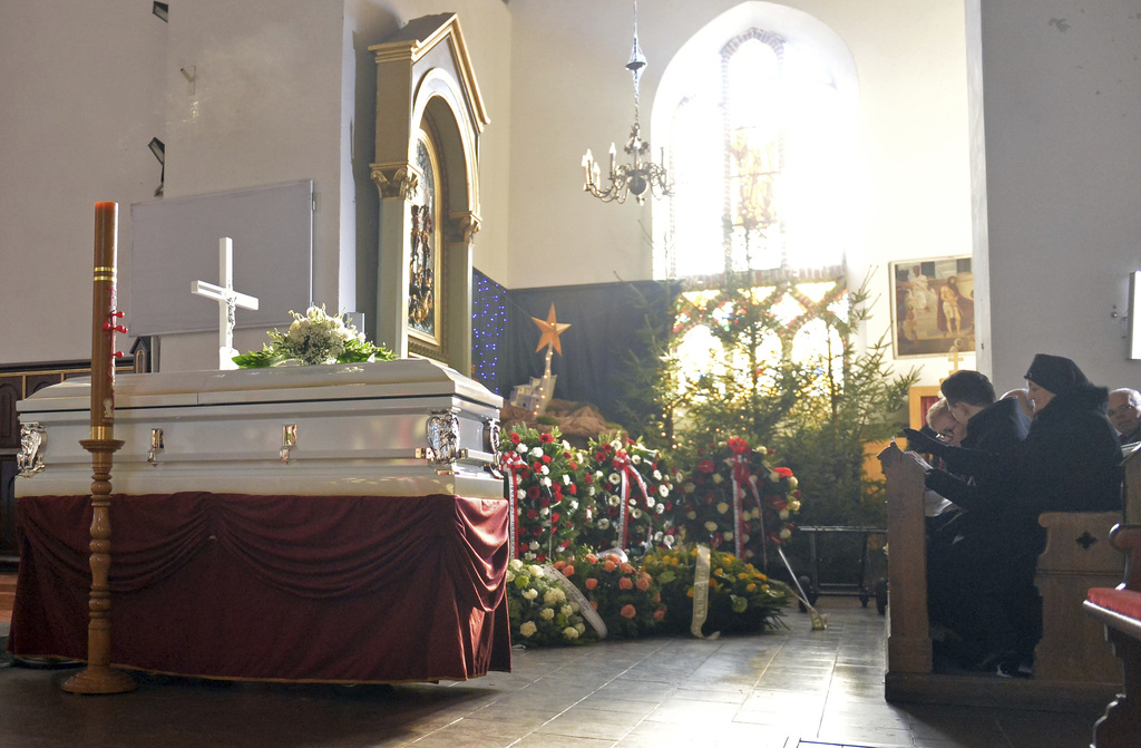 People pray in front of the coffin with the body of Lukasz Urban, the Polish truck driver killed in the Berlin Christmas market attack,...