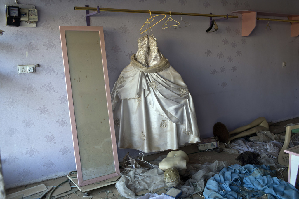 FILE - A wedding gown stands in a beauty parlor damaged in clashes between Iraqi security forces and Islamic State fighters in Bartella...