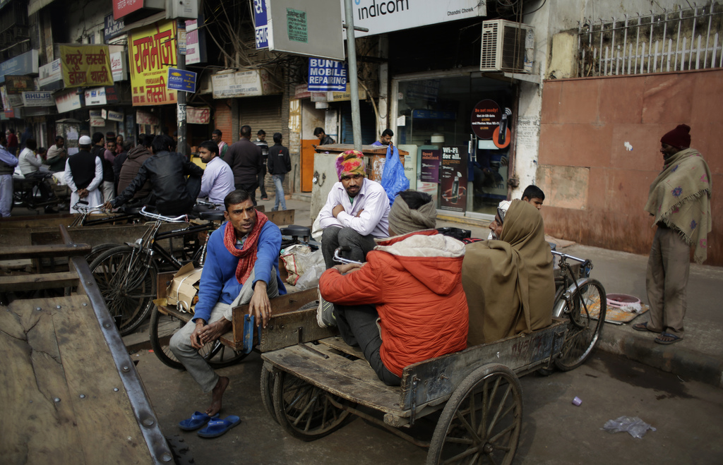 Indians daily wage workers sit on cycle rickshaws while waiting for work at a market place in New Delhi, India, Friday, Dec. 30. 2016. ...