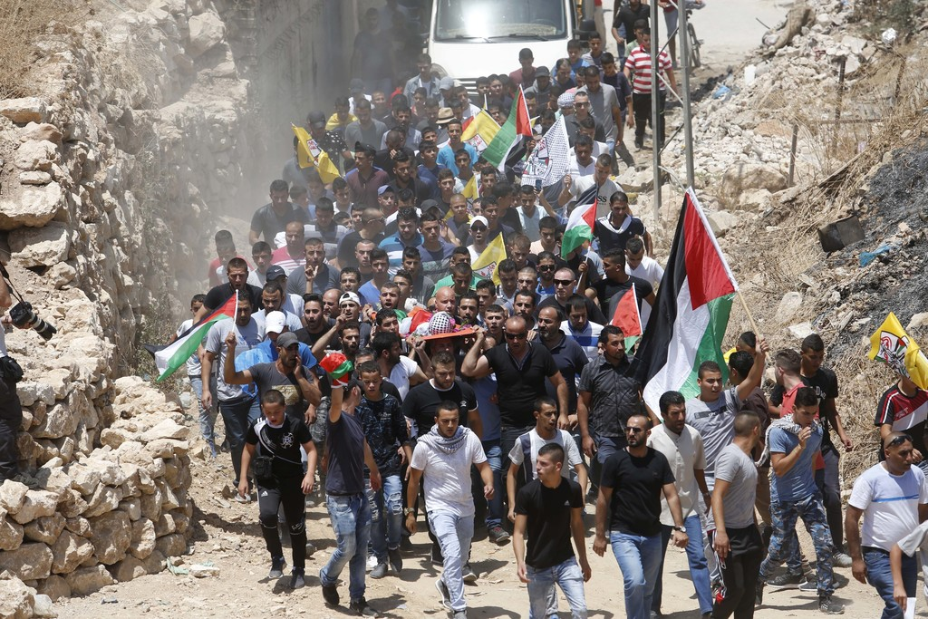 FILE - Mourners carry the body of Muhey al-Tabakhi, 12, during his funeral in the West Bank town of Al-Ram, near Jerusalem, Wednesday, ...