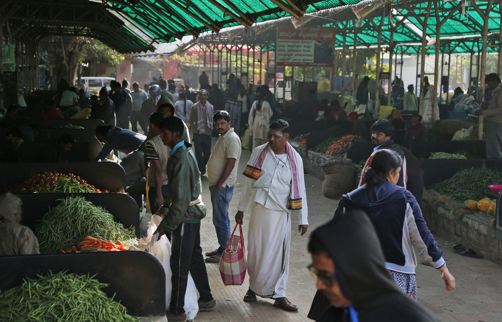 People shop at a wholesale vegetable market in Bangalore, India, Friday, Dec. 30, 2016. India yanked most of its currency bills from ci...