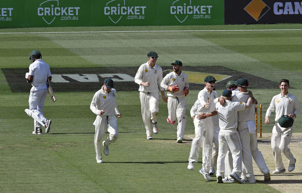Australian players congratulate Mitchell Starc after bowling out Pakistan's Wahab Riaz, left on the fifth day of their second cricket t...