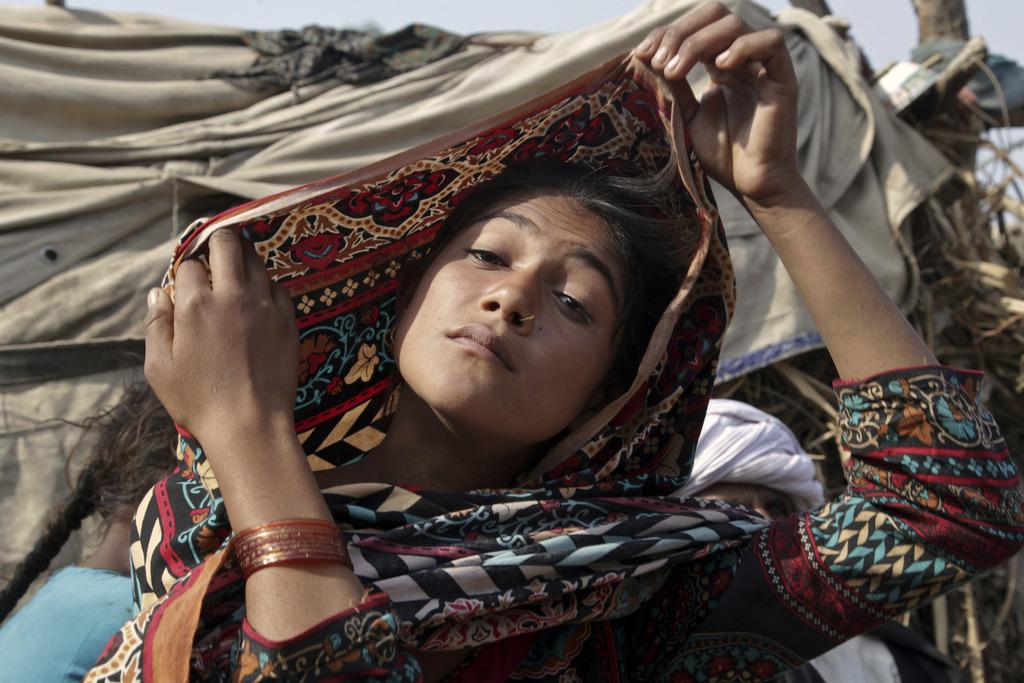 In this Tuesday, Dec. 20, 2016 photo, Saima, who married an o;der man in her early teens, fixes her scarf during an interview in Jampur...