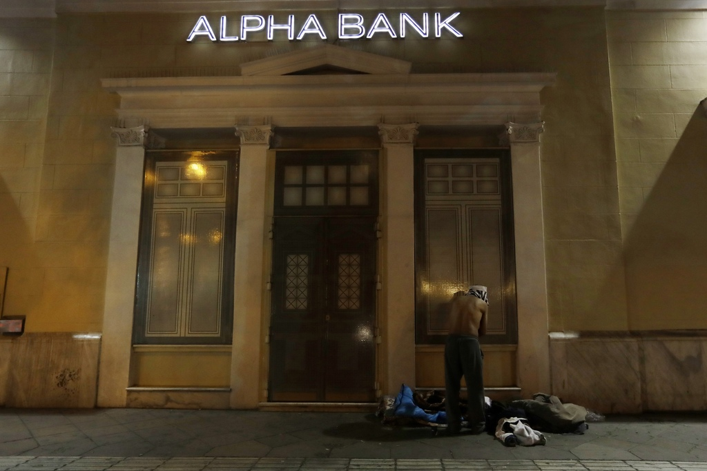 In this photo taken on Wednesday, Dec. 21, 2016, a homeless person changes clothes outside a bank in central Athens. Nearly one-in-four...