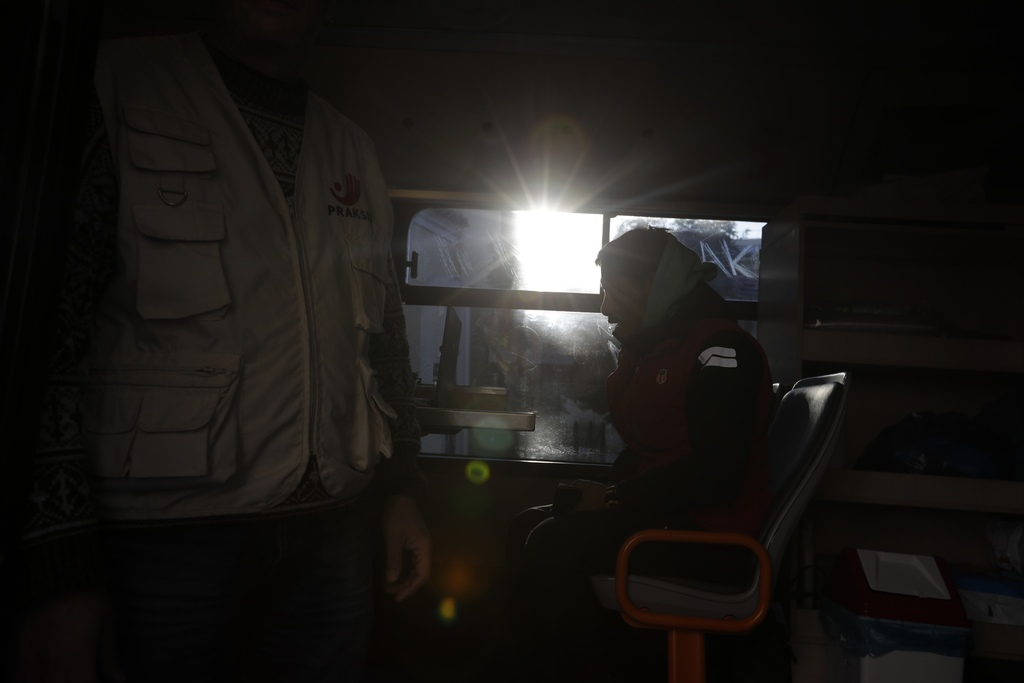 In this photo taken on Monday, Dec. 19, 2016, a homeless person talks with a social worker on a shower bus run by the Greek Praksis, No...