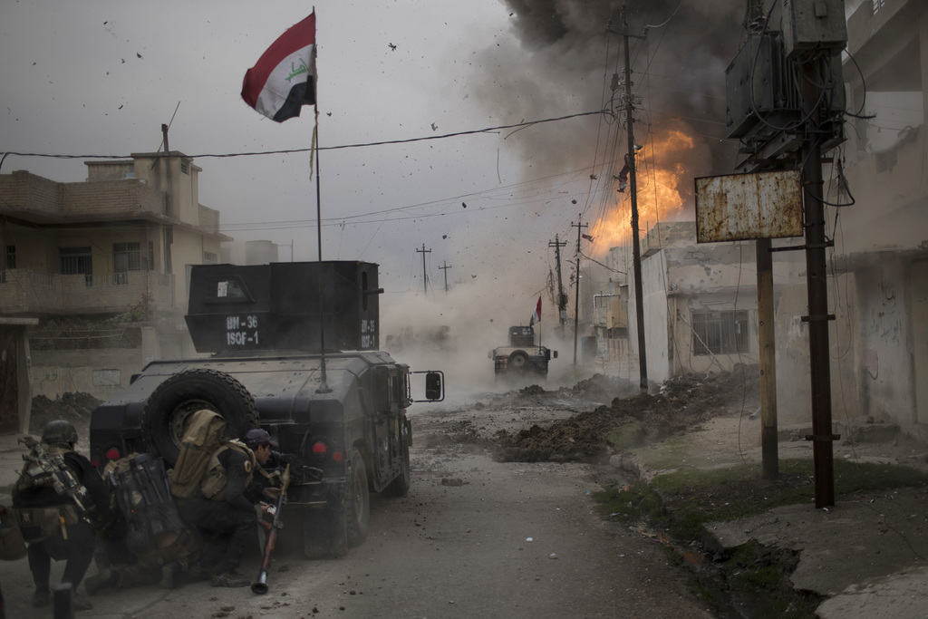 FILE - A car bomb explodes next to Iraqi special forces armored vehicles as they advance towards Islamic State militant- held territory...