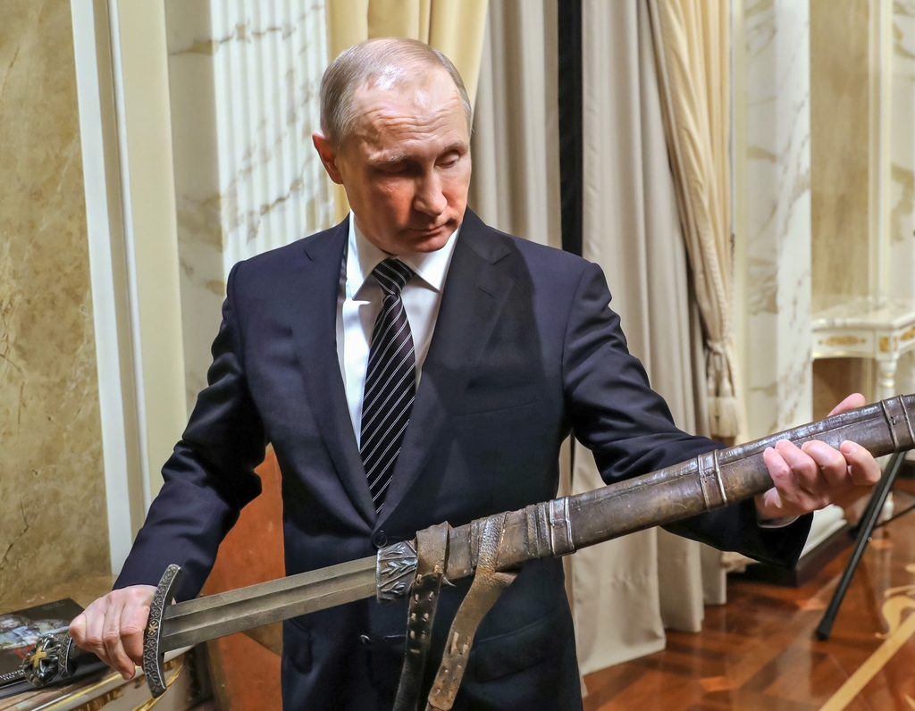 Russian President Vladimir Putin holds a sword while listening an explanations from the head of Russian First Channel Konstantin Ernst,...