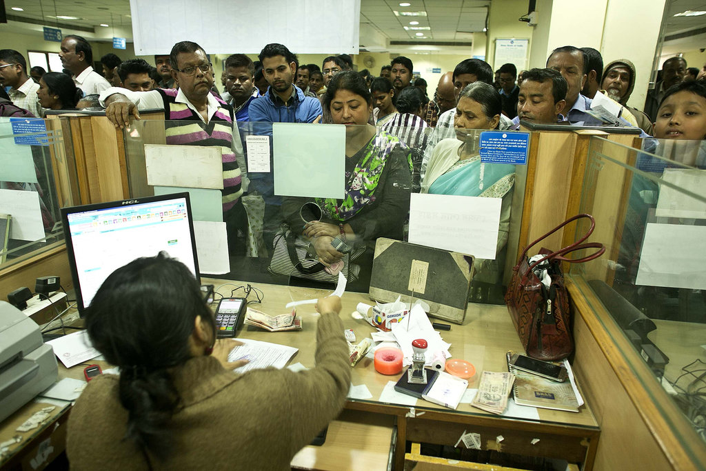 Indians deposit discontinued notes on the last day in a bank in Gauhati, India , Friday, Dec. 30, 2016. India yanked most of its curren...