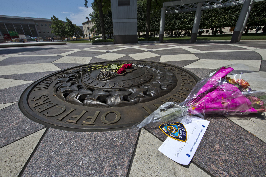 FILE - In this July 8, 2016 file photo, five red roses on the bronze medallion with another bouquet of flowers and a note in support of...