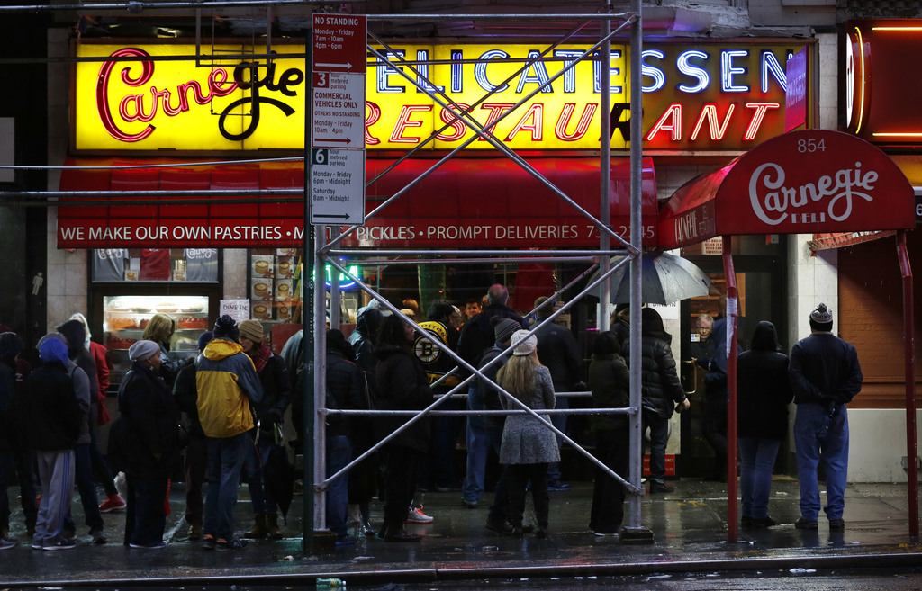 People wait in line to eat at the Carnegie Deli in New York, Thursday, Dec. 29, 2016. After 79 years of serving up heaps of cured meat,...