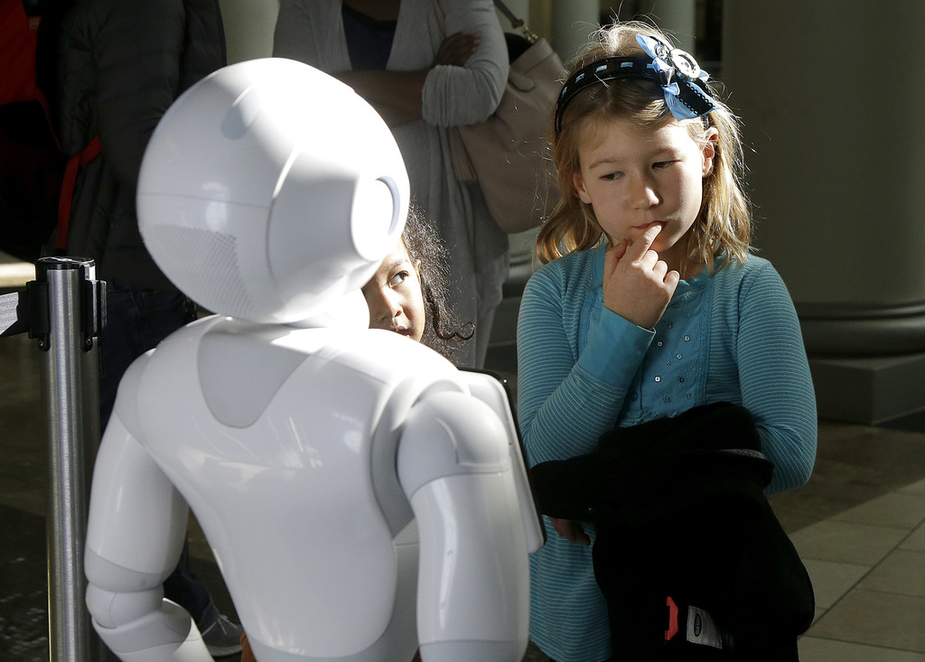 In this Thursday, Dec. 22, 2016, photo, Emerson Hill, 6, plays with Pepper the robot at Westfield Mall in San Francisco. While merrily ...
