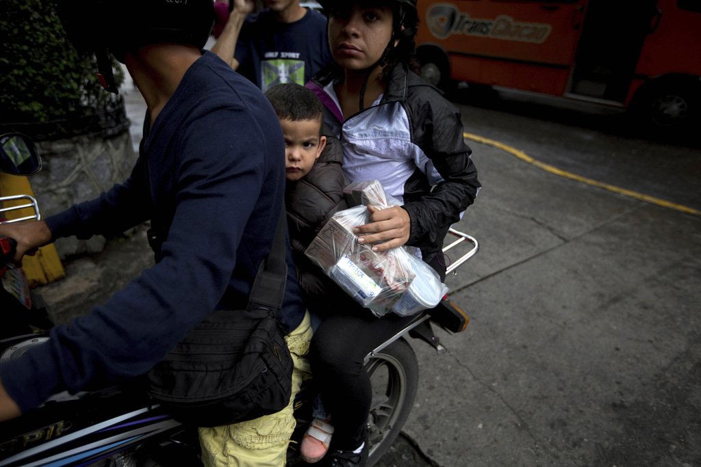 In this Dec. 9, 2016 photo, a family leaves a pharmacy after buying soap and toothpaste on the east side of Caracas, Venezuela. The ris...