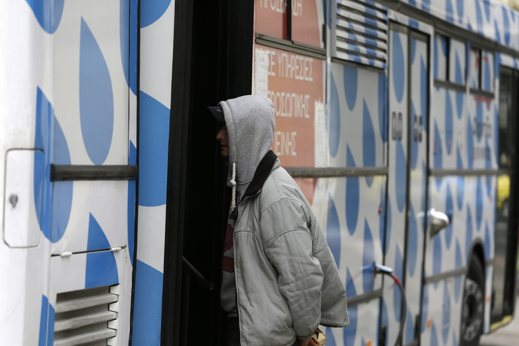In this photo taken on Wednesday, Dec. 21, 2016, a homeless person asks for information a social worker at the shower bus run by the Gr...