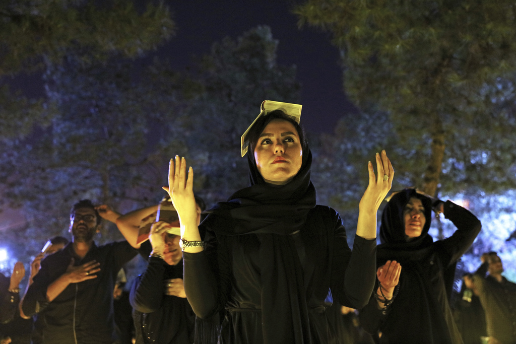 FILE - Iranian Shiite Muslims pray as they place the Quran on their heads at the graves of soldiers who were killed during 1980-88 Iran...