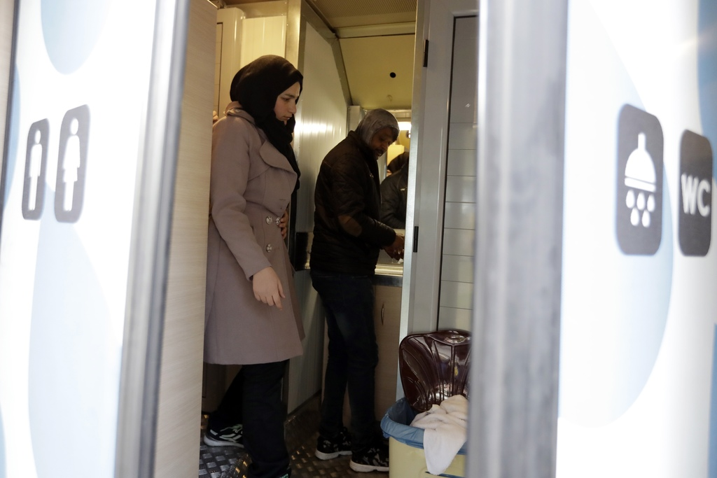 In this photo taken on Wednesday, Dec. 21, 2016, a homeless person and a woman use the shower, run by the Greek Praksis ,Non Government...