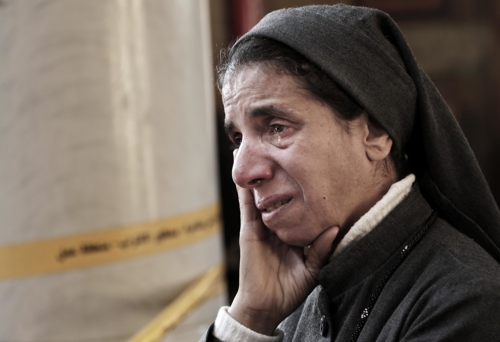 FILE - An Egyptian Coptic nun weeps as she looks at damages inside the St. Mark Cathedral in central Cairo, following a bombing, Sunday...