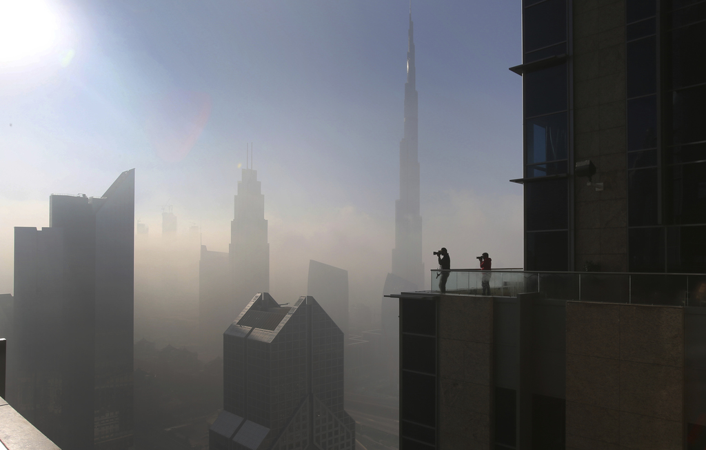 People take pictures at balcony on the 42nd floor of a building on a foggy day in Dubai, United Arab Emirates, Friday, Dec. 30, 2016. (...