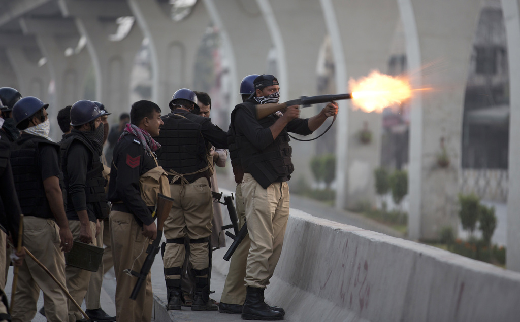 FILE - A Pakistani police officer fires tear gas shell to disperse crowd protesting against the government in Rawalpindi, Pakistan, Fri...