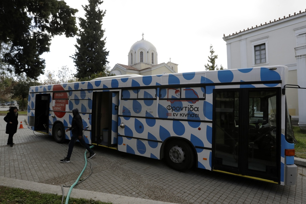 In this photo taken on Wednesday, Dec. 21, 2016, a homeless person leaves the shower bus run by the Greek Praksis,Non Governmental Orga...