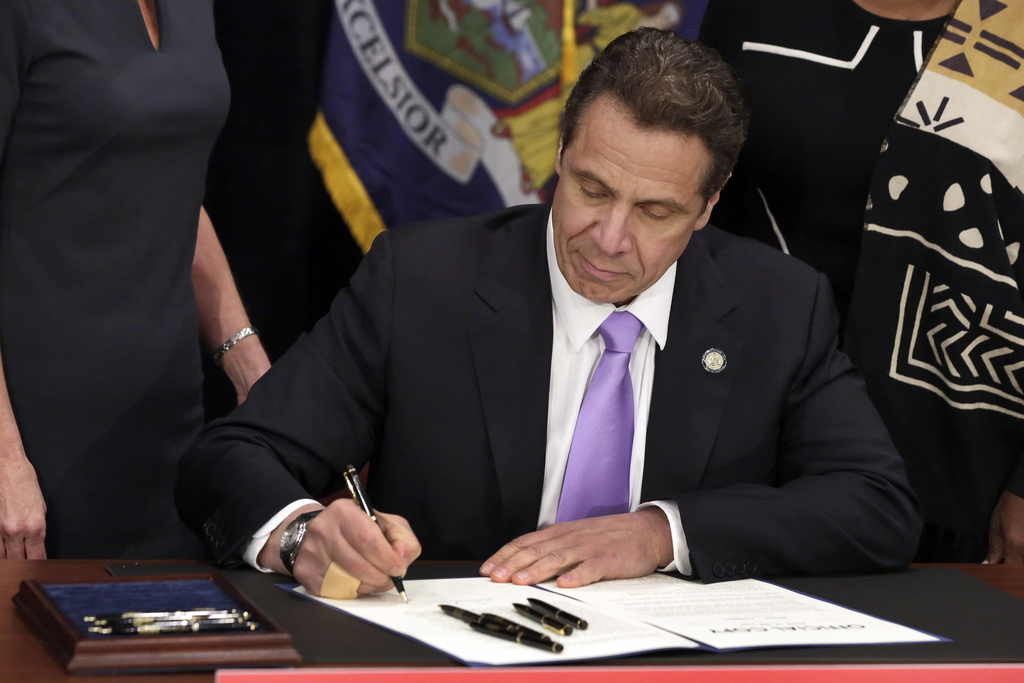 FILE- In this April 4, 2016 file photo, New York Gov. Andrew Cuomo signs a law that will gradually raise New York's minimum wage to $15...