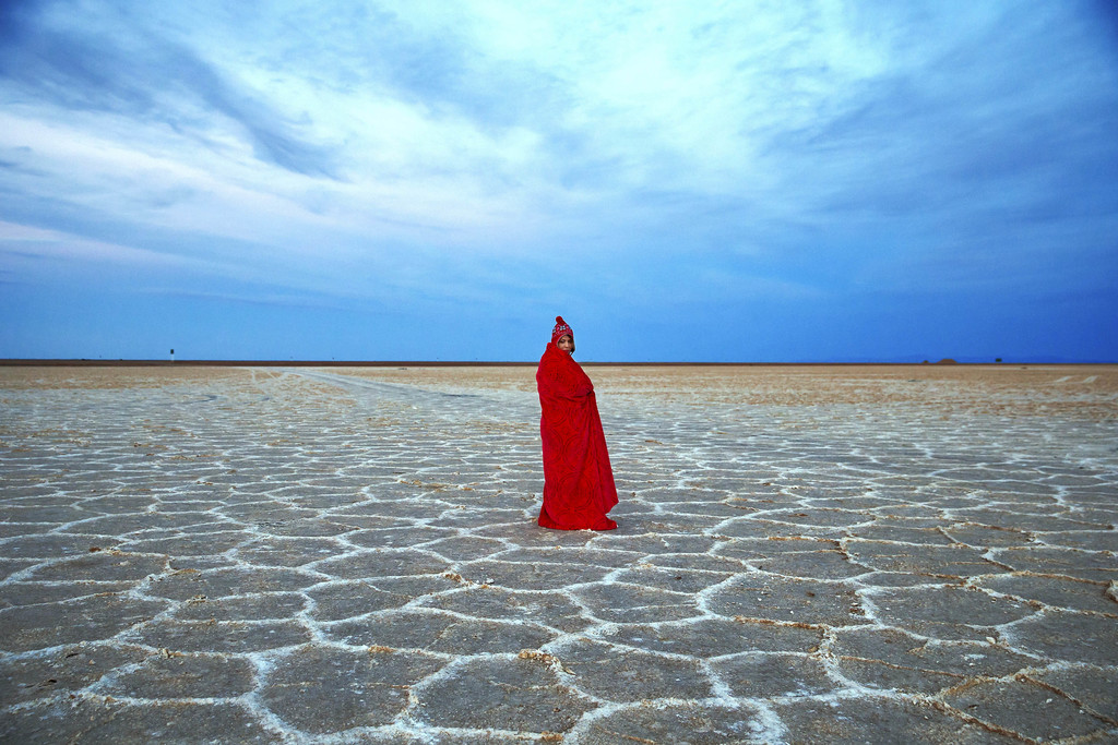 FILE - In this picture taken on Thursday, Dec. 1, 2016, an Iranian woman covers herself with a blanket due to the cold, while visiting ...