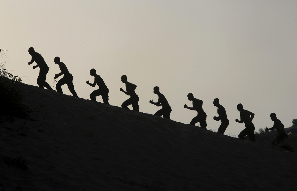 FILE - FILE - FILE - Palestinian students march during sunset in a display of their military skills at Al-Rebat College for Law and Pol...