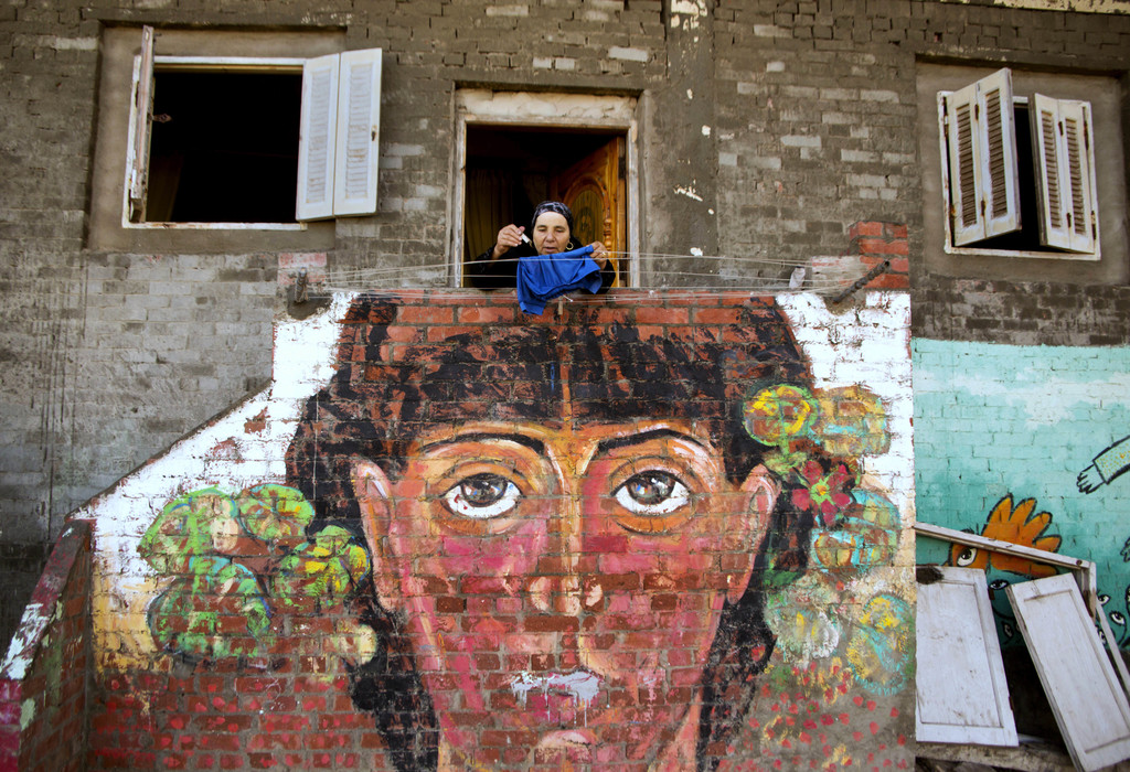 FILE - In this Thursday, Oct. 13, 2016 photo, an Egyptian woman hangs her laundry over a mural by Egyptian artist Omar El Fayoumi in Bu...