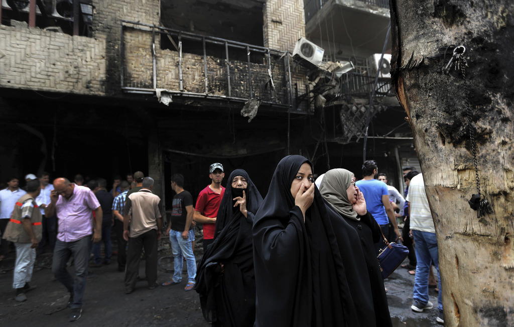 FILE - Iraqi women wait to hear about family members who went missing after a car bomb hit Karada, a busy shopping district in the cent...