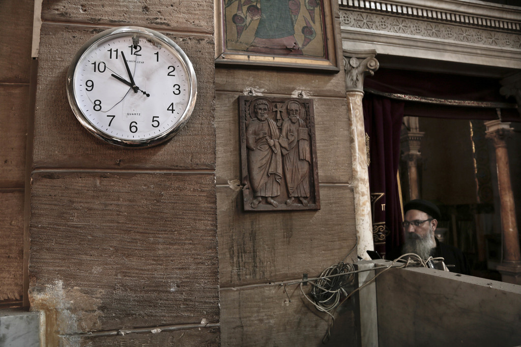 FILE - A damaged clock and Coptic clergyman at the scene inside the St. Mark Cathedral in central Cairo, following a bombing, Sunday, D...