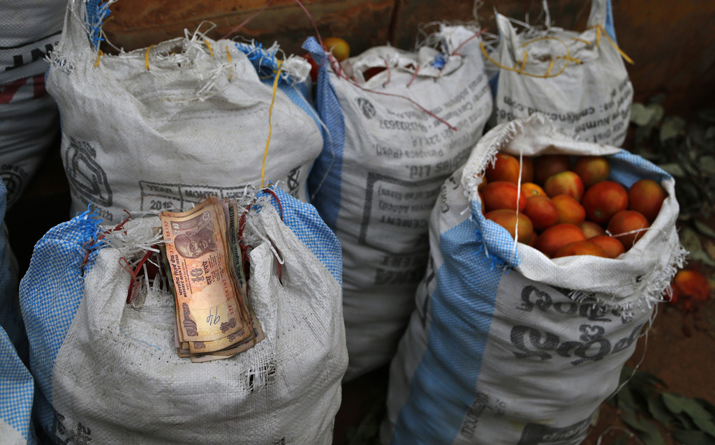 Smaller denomination currency notes are placed on a sack of tomatoes, put up for sale at a wholesale vegetable market in Bangalore, Ind...