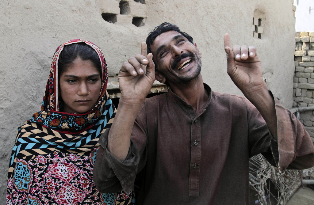 In this Tuesday, Dec. 20, 2016 photo, Mohammad Ramzan, right, reacts while talking to The Associated Press with his young bride Saima i...