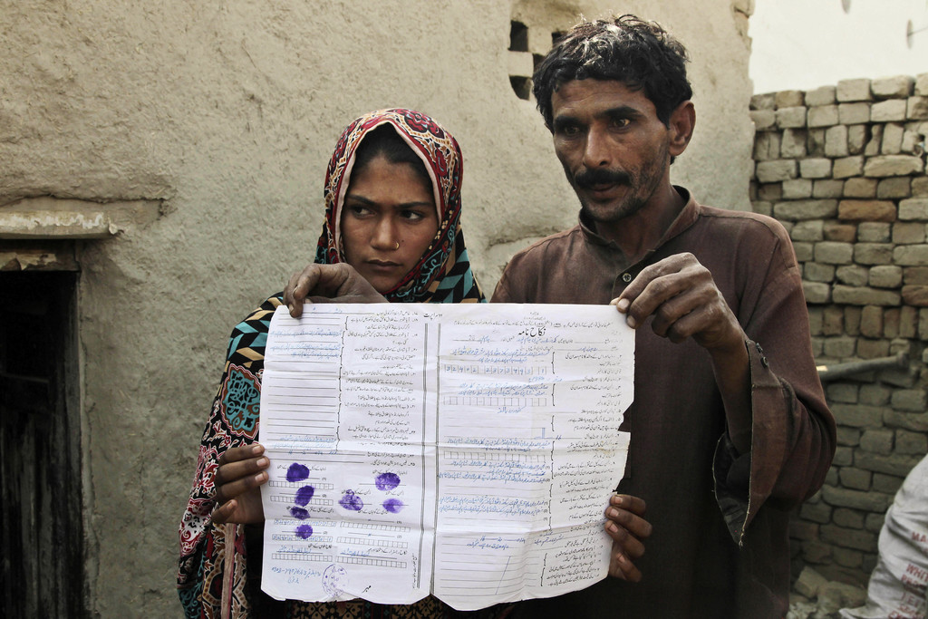 In this Tuesday, Dec. 20, 2016 photo, Mohammad Ramzan shows his marriage contract with his young bride Saima in Jampur, Pakistan. Saima...