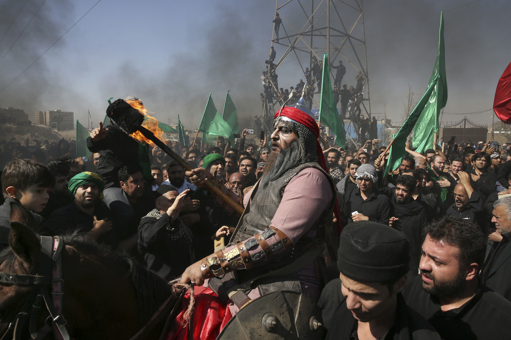 FILE - A Shiite re-enacts the events of Ashoura while Iranian and Iraqi Shiite Muslims mourn in a procession in southern Tehran, Iran, ...
