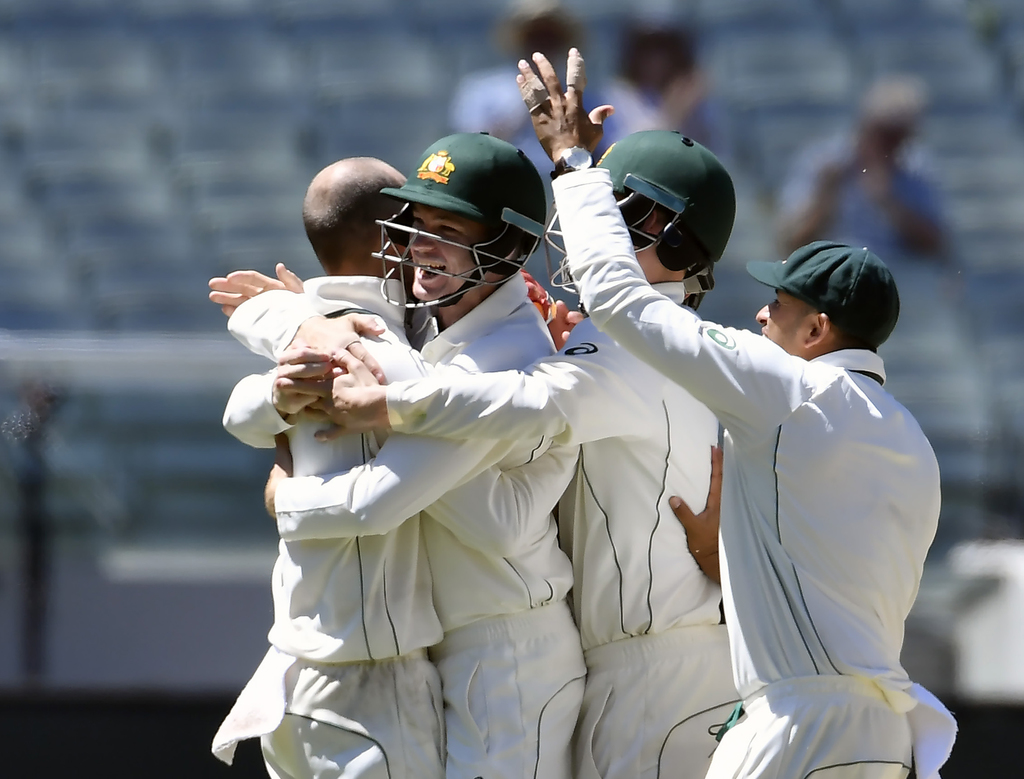 Australia's Nathan Lyon, left, and Peter Handscomb celebrate capturing the wicket of Pakistan's Asad Shafiq on the fifth day of their s...