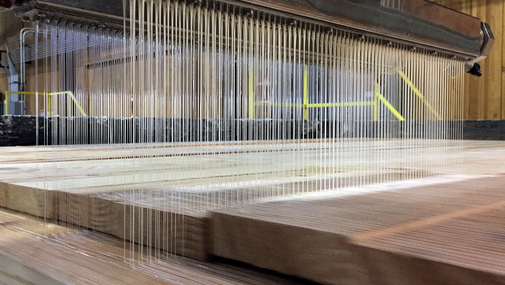 In this Nov. 11, 2016 photo, a machine applies glue to the next layer of a panel of cross-laminated timber, or CLT, in the production f...